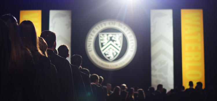 Shadow of students in line at convocation with the University of Waterloo emblem in the background