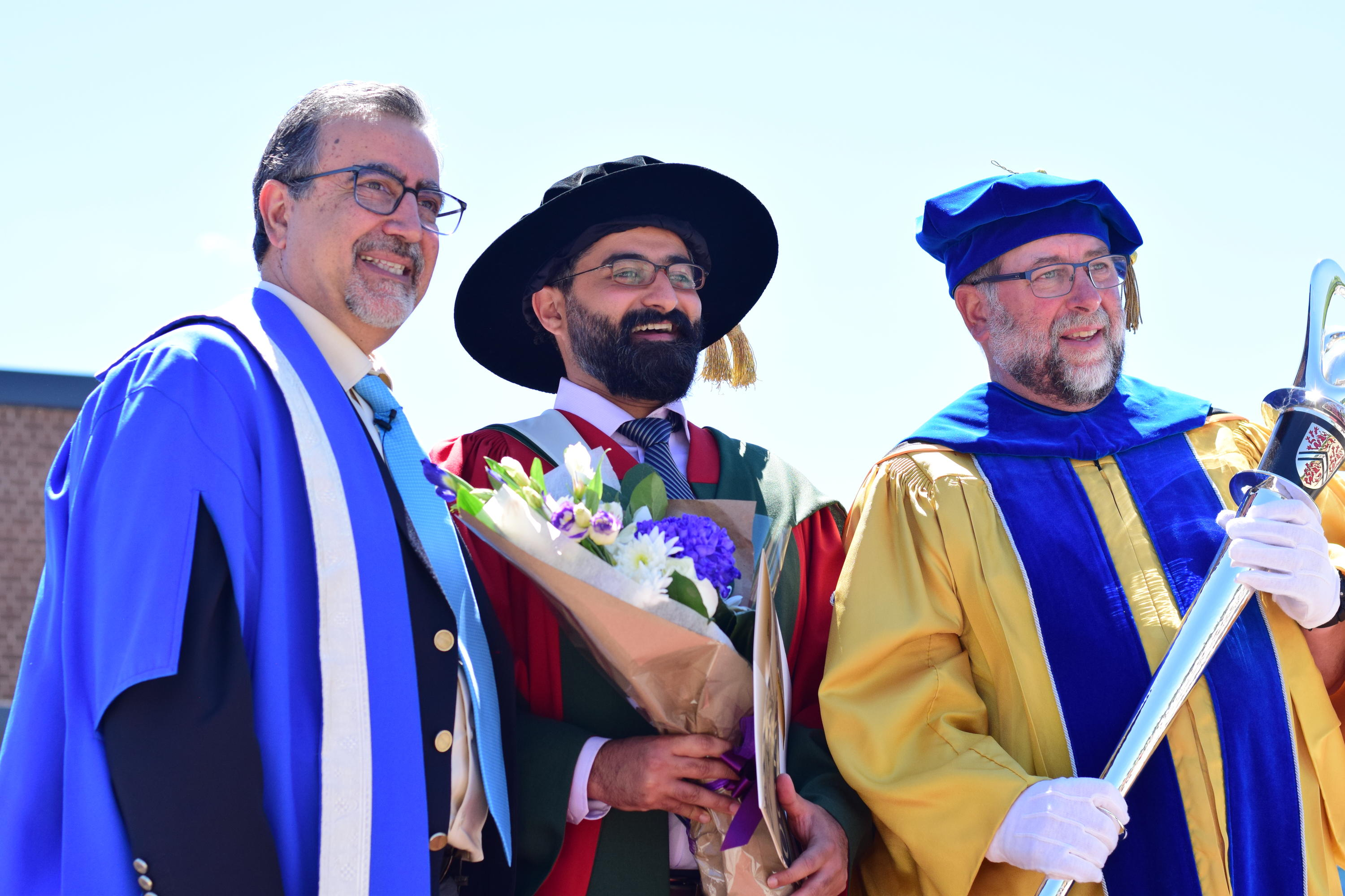 Feridun Hamdullahpur poses with members of the academic procession.