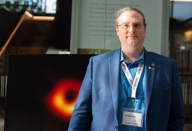 Professor Avery Broderick standing in front of a poster of the image of black hole M87*