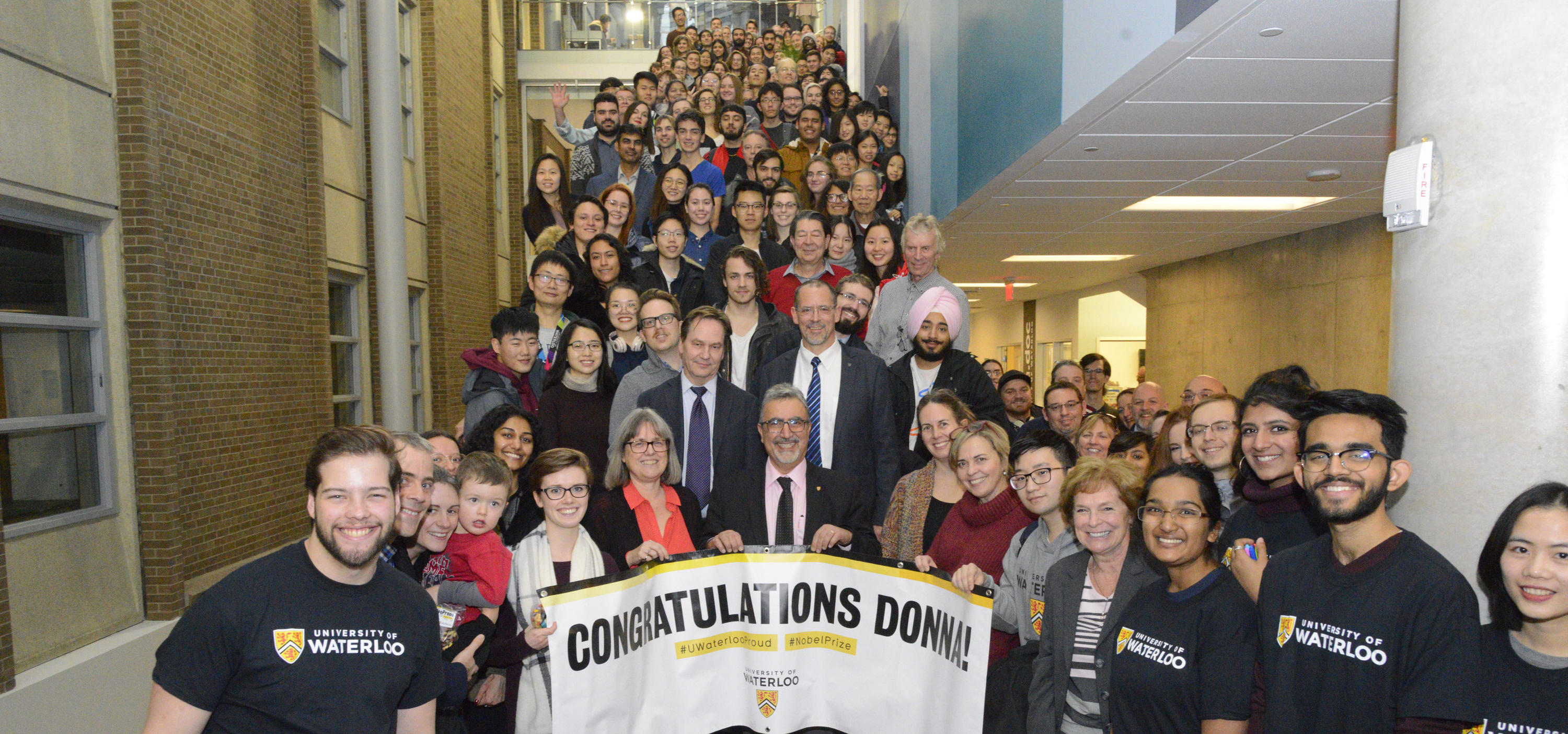 A group photo of attendees with Donna Strickland and the UW President holding a Congratulations Donna banner.