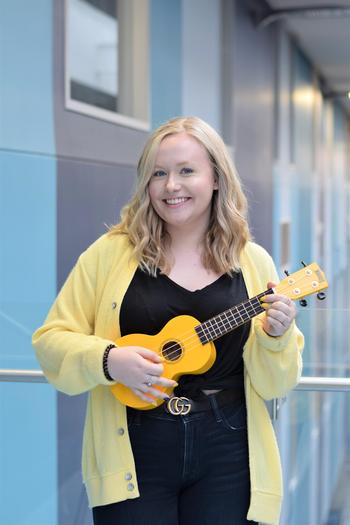 Hayley holding a yellow ukulele