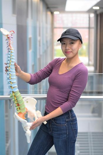 Jenny holding a model of a human spine