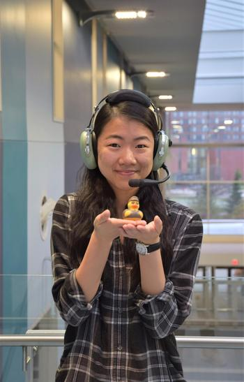 Joy wearing a pilot headset and holding a rubber duck