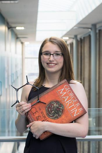 Julia holding a large book and a black cyclic compound made of plastic