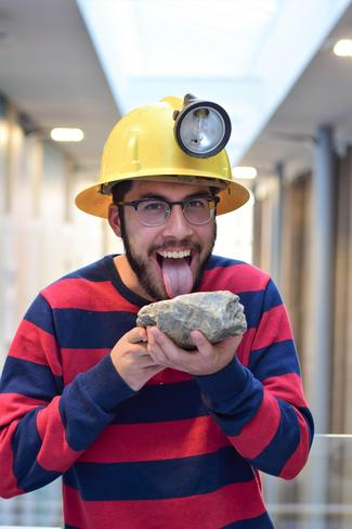 Kaden wearing a yellow miner's hard hat while holding a rock and pretending to lick it