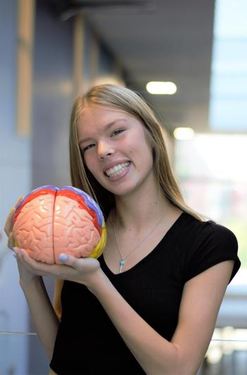 Kaitlynn holding a model of a brain