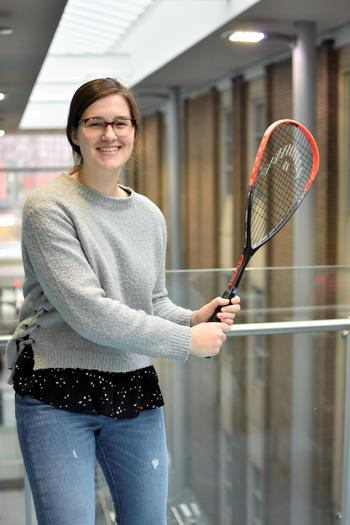 Lindsay smiling and holding a squash racquet