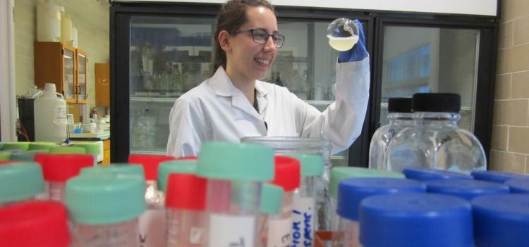 Ola Matysiakiewicz holding a flask in the lab.