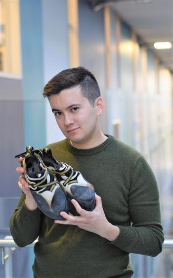 Sebastien holding his rock climbing shoes