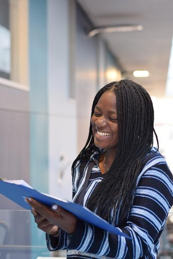 Temi looking at a clipboard and smiling