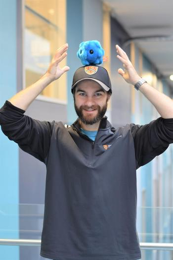 Tim holding a plushy bacteria over his head