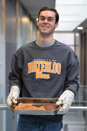 """William wearing a """"Waterloo Mom"""" sweater and holding a batch of cookies"""