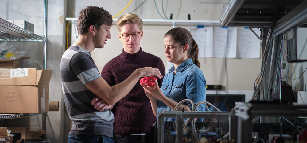 Prof Crystal Senko showing an ion trapping device to two students.