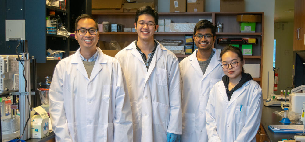 Professor Emmanuel Ho and three graduate students in the lab.