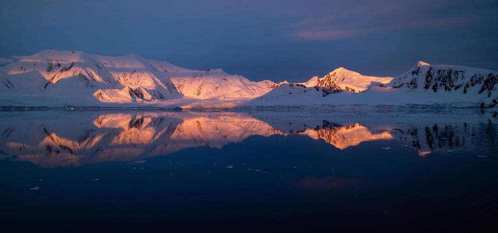 Snow covered mountain range with reflection in water in Antarctica