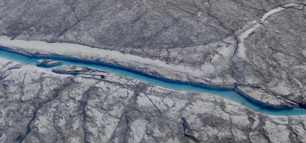 Greenland's Dark Zone, showing dark sediment across the top of the ice sheet and a river winding through the ice