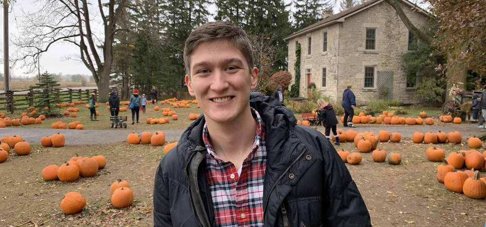 Matthew Schmitz standing in a pumpkin field, with a stone house in the background