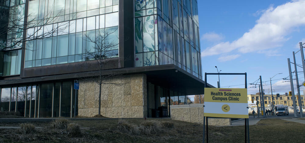 School of pharmacy building with sign pointing to Health Sciences Campus Clinic