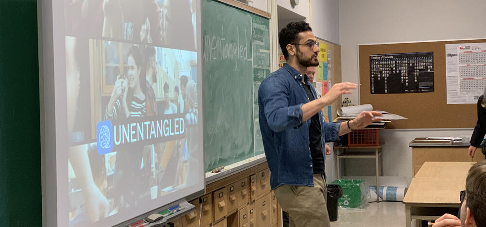 Shayan Majidy standing at the front of a classroom talking to students