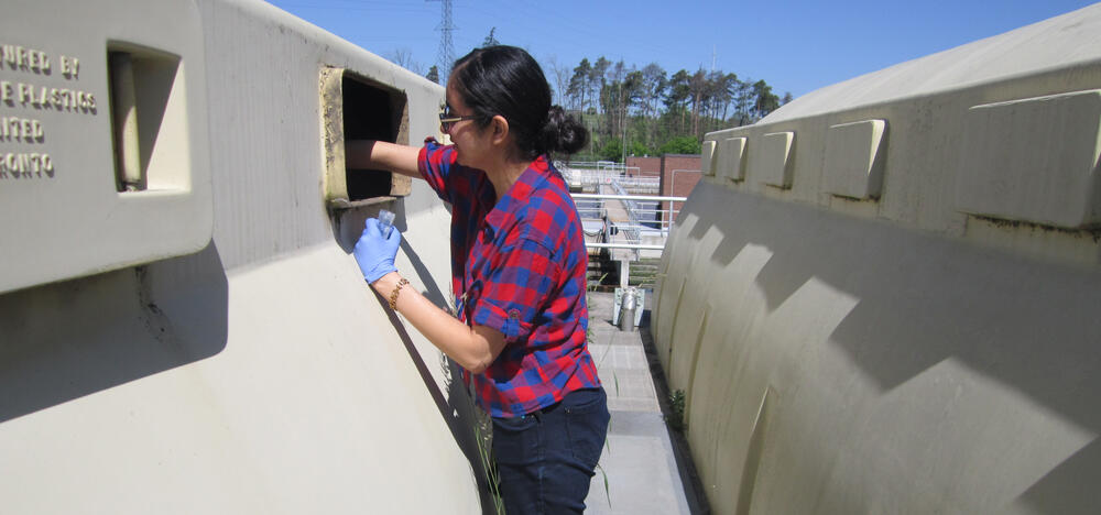 Sarah Al-Ajeel sampling wastewater from a treatment plant site