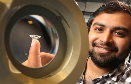 Waterloo Science alumnus Harry Gandhi holding his smart contact lens