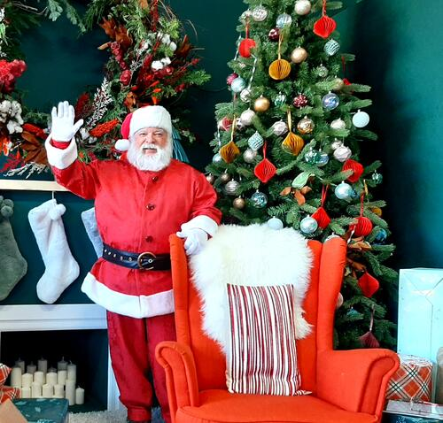 Santa standing in front of a decorated Christmas tree and fireplace, waving at the camera