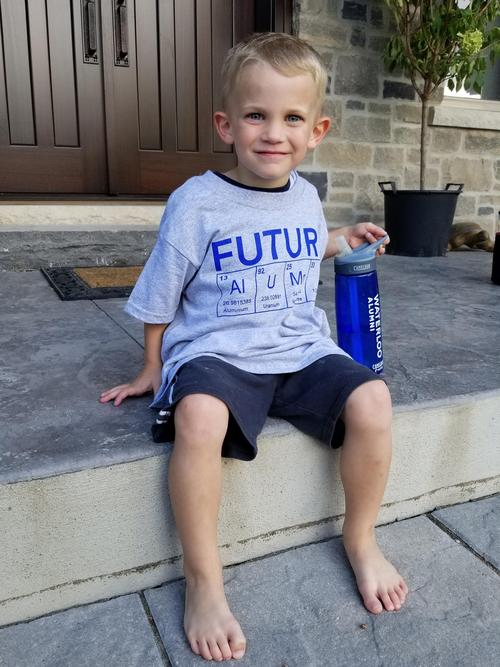 smiling boy wearing future science alumni t shirt