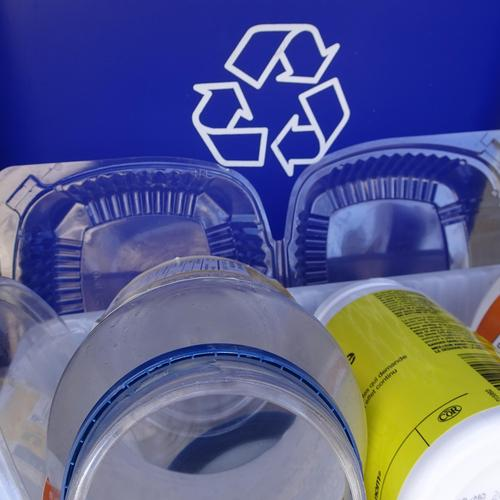 plastc containers beside a recycling bin