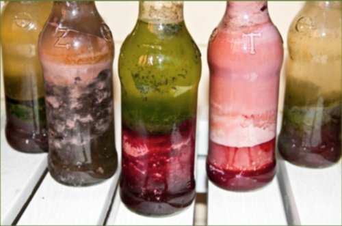 clear glass containers filled with colourful bands of mud