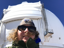 Alex Krolewski in front of a white observatory dome