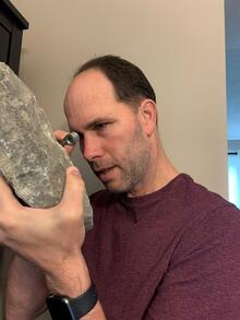 John Johnston looking at a large rock with a hand lens.