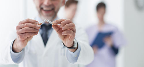 Stock image of person breaking a cigarette with two medical professionals talking blurred in the background.