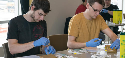 Two male pharmacy students learning how to administer vaccinations.