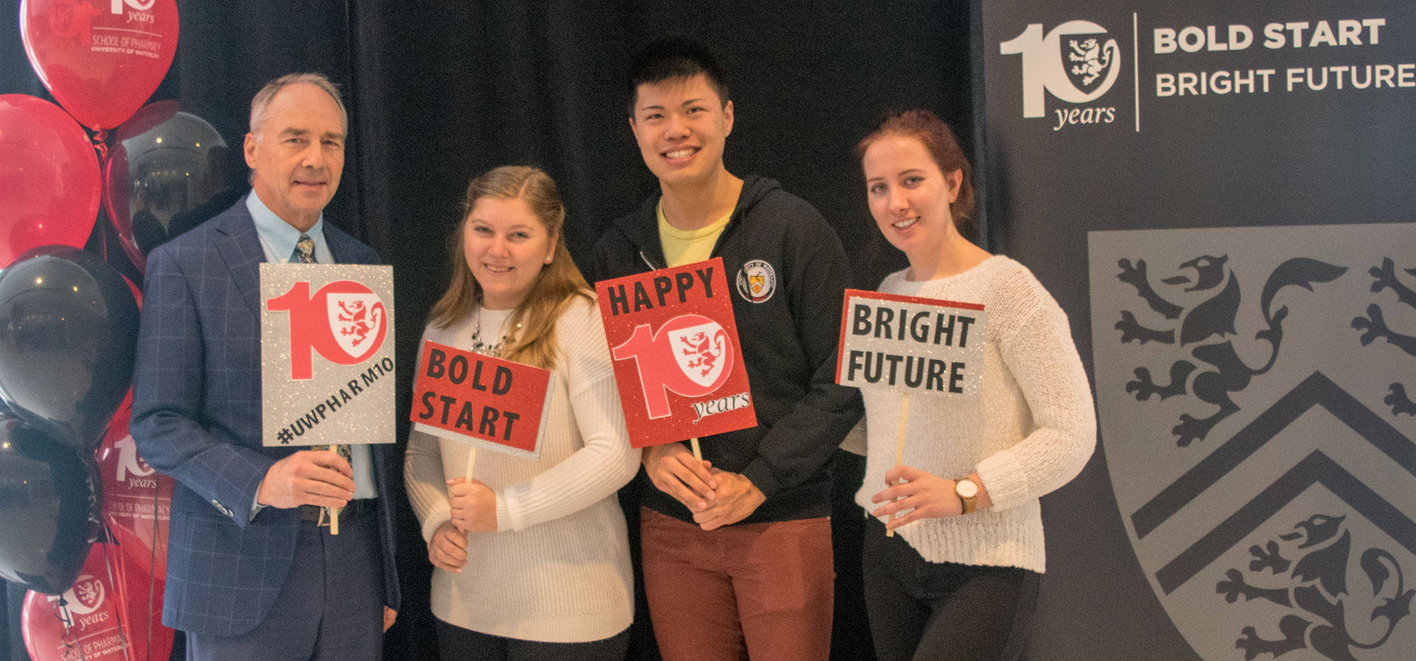 Dave Edwards and 3 students smiling with Bold Start and Bright Future signs.
