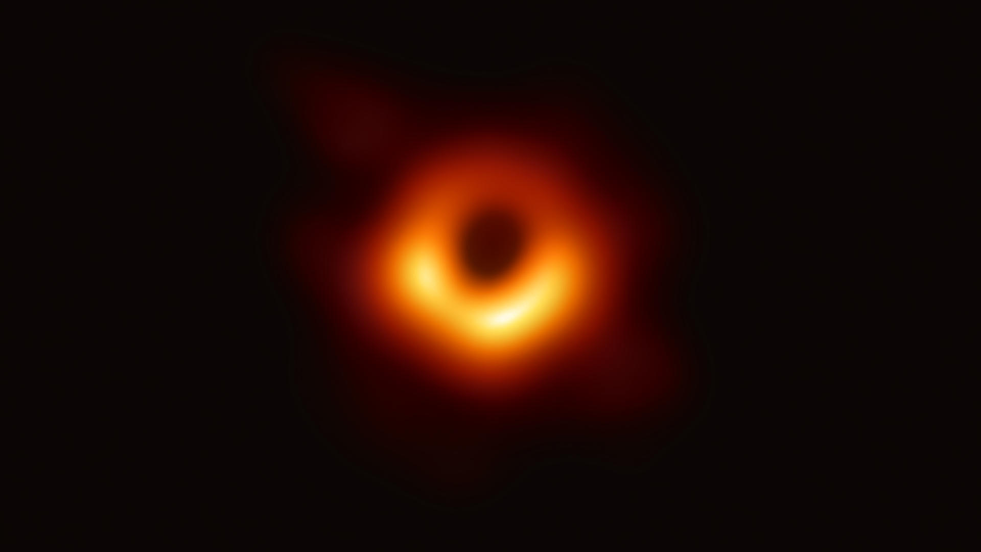 Black hole image, showing a red and orange circle of light before it has crossed the event horizon