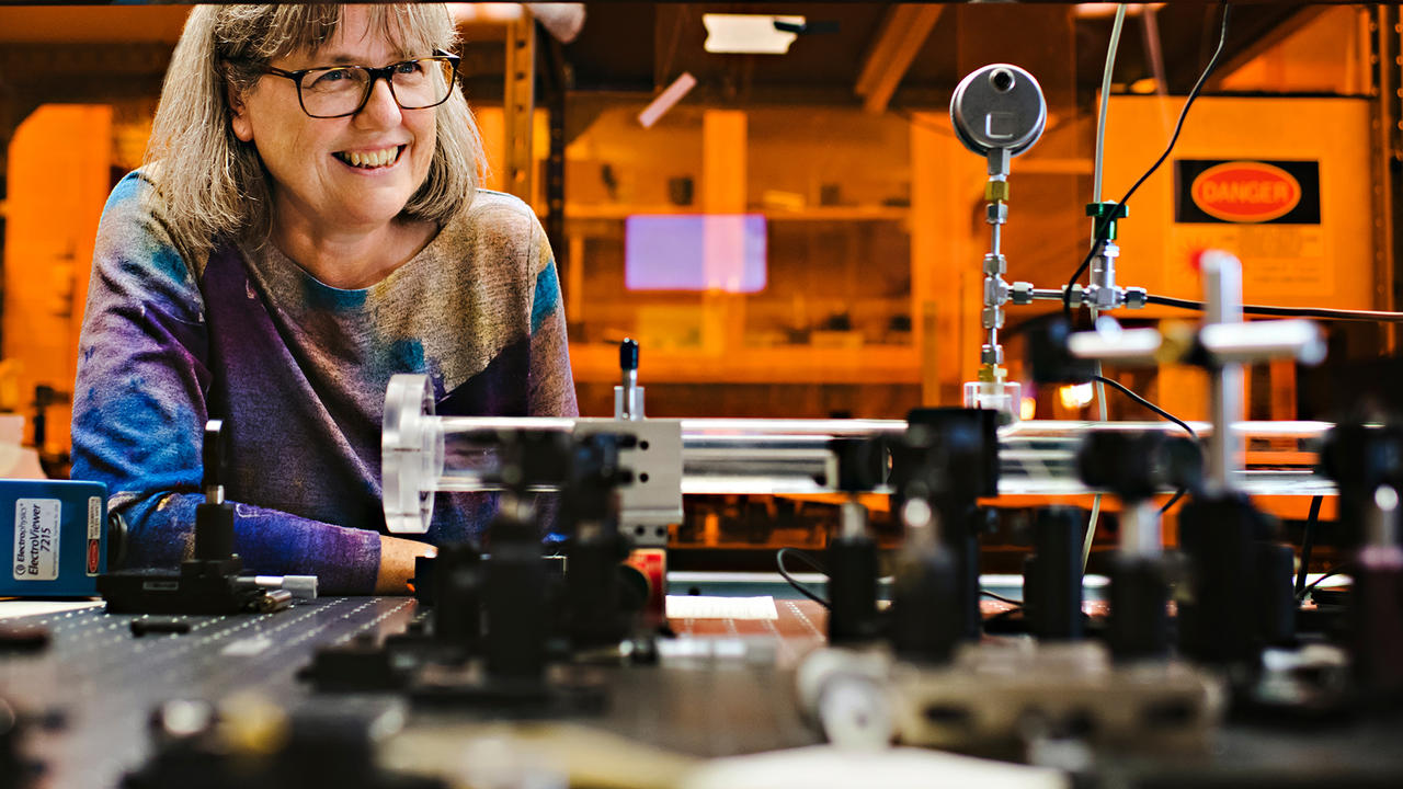 Donna Strickland leans on lab table with laser equipment.