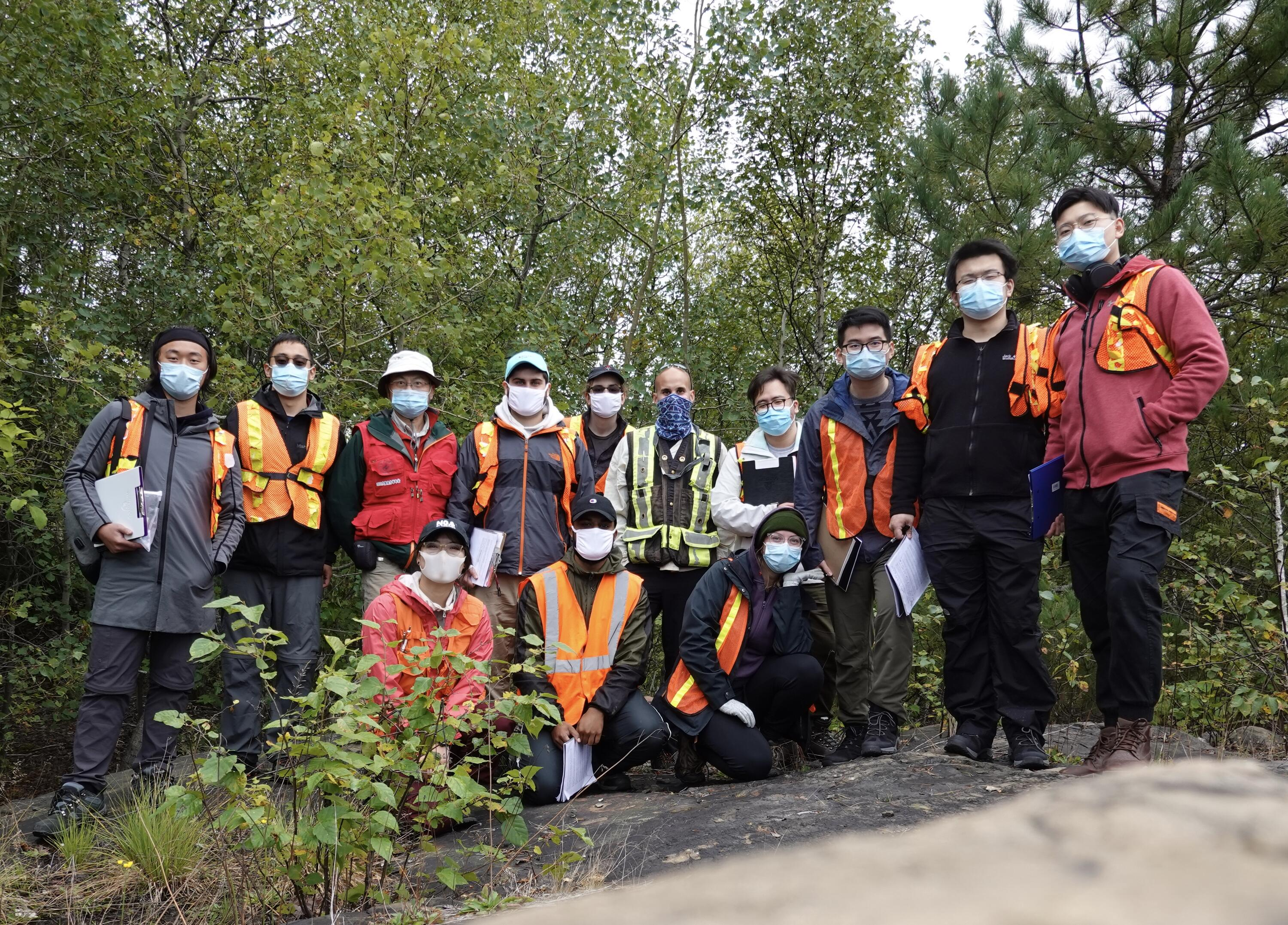 Group of students, TAs, and professor standing on a rock surrounded by trees. All are wearing masks