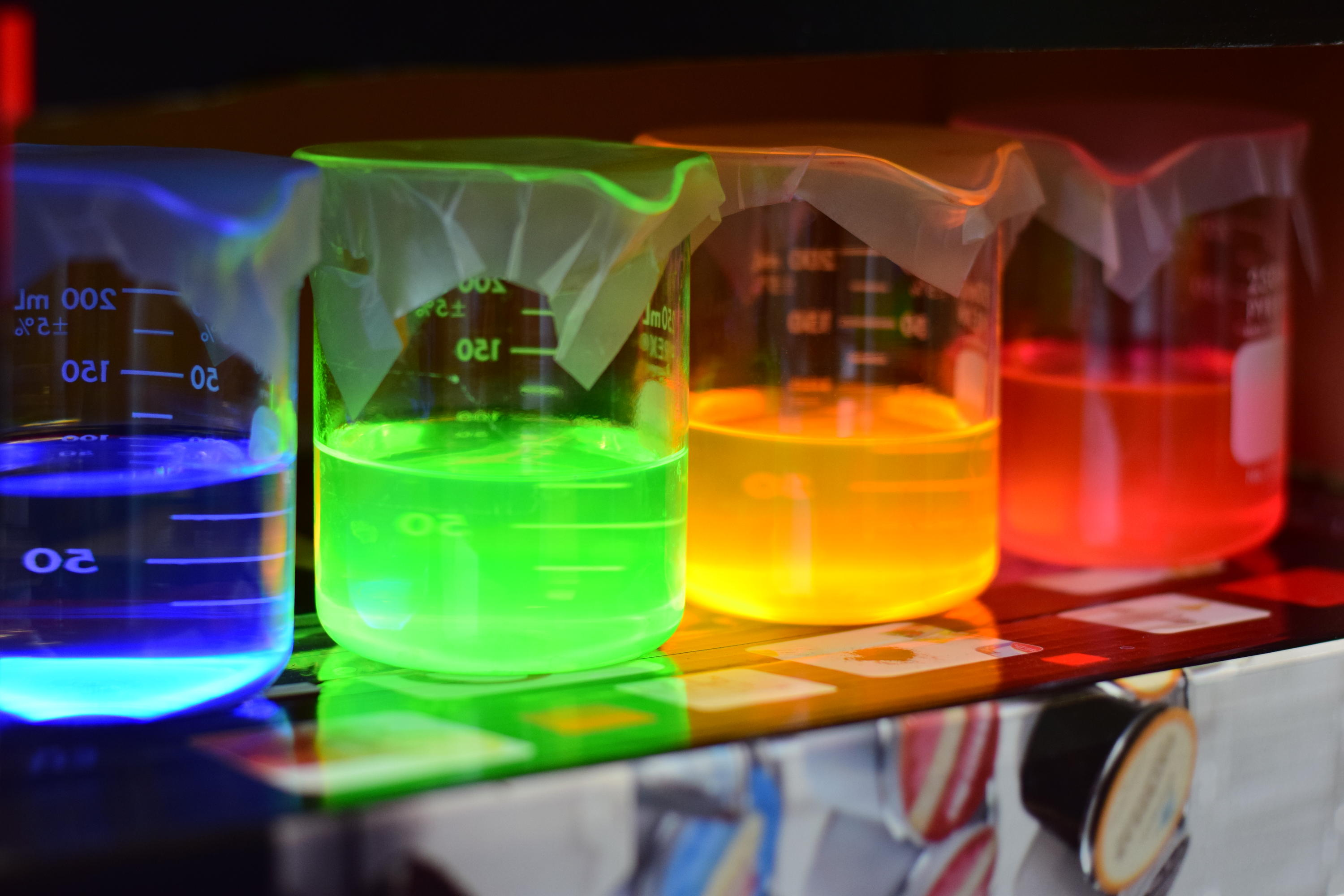Row of colourful luminescent beakers