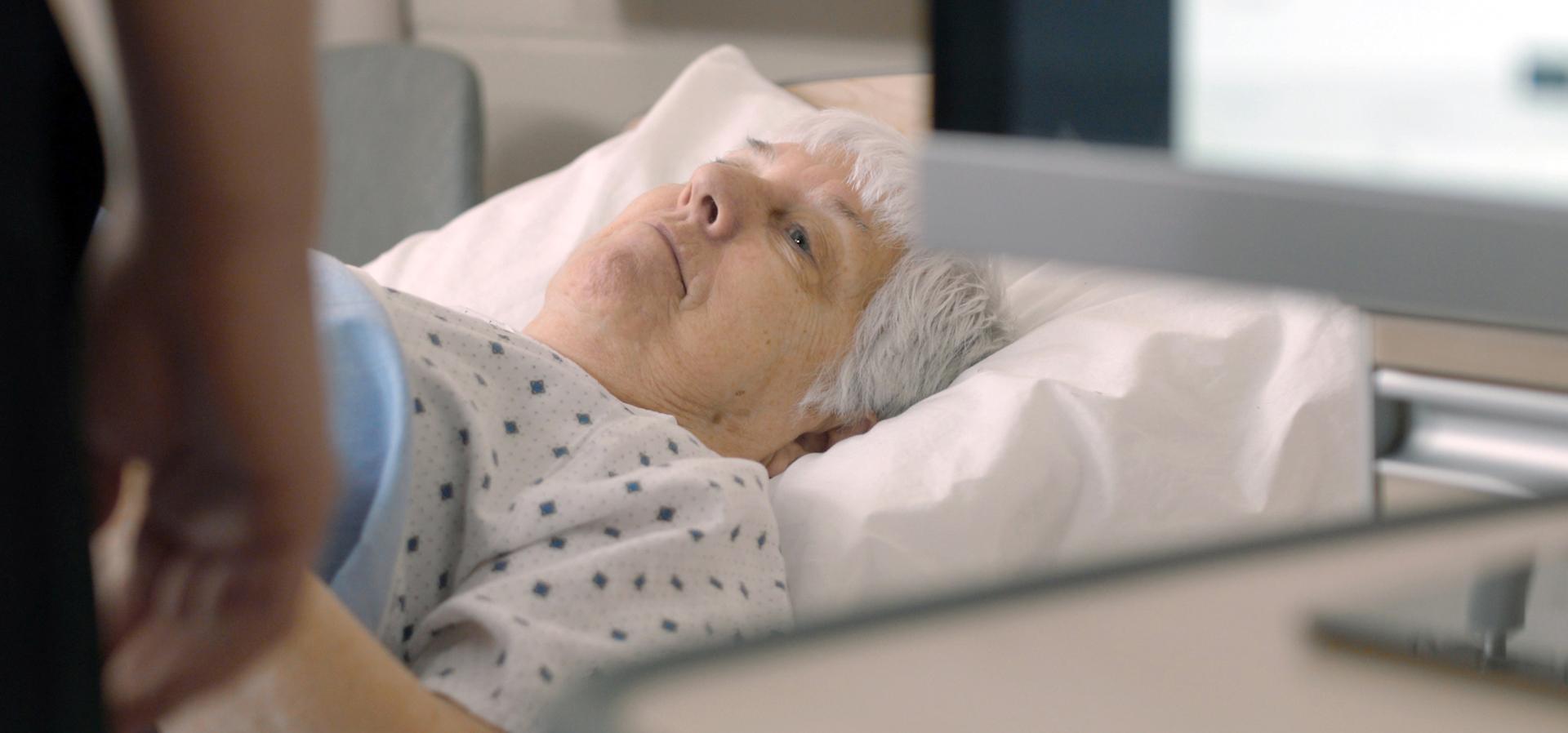 Elderly women lies in a hospital bed