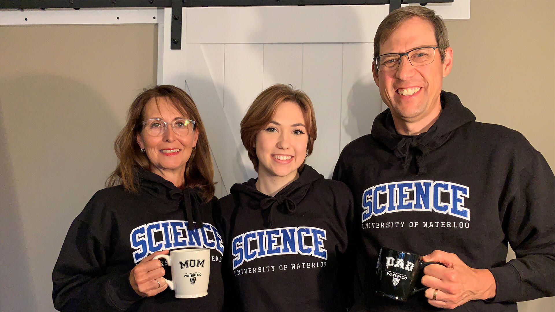 Jocelyn Hadden with her parents Susan and James, all in Waterloo Science sweaters.