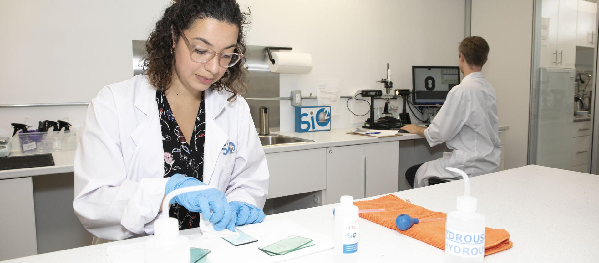 Female working in at a lab bench with male at fume hood in background