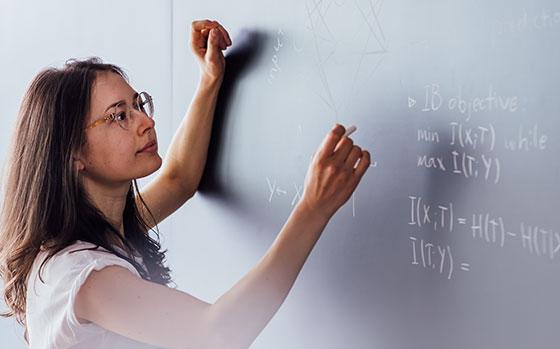 Anna Golubeva writing with chalk on a black board.