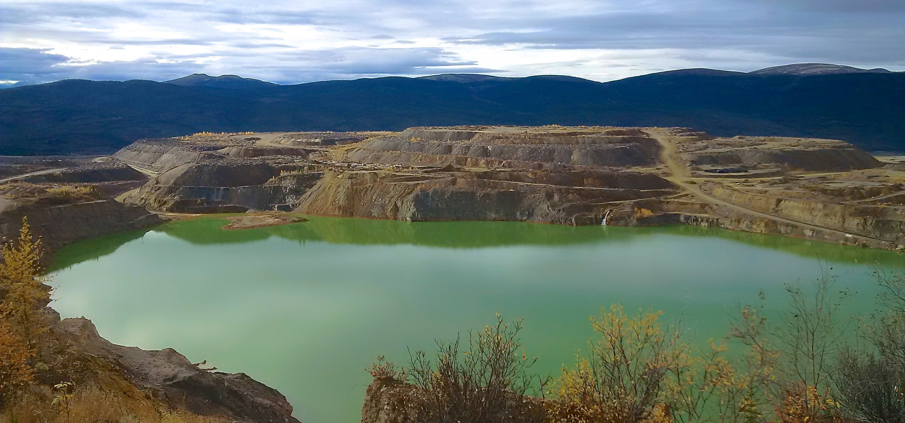 Flooded open pit at the Faro Mine, Yukon Territory, with waste-rock stockpiles in background.