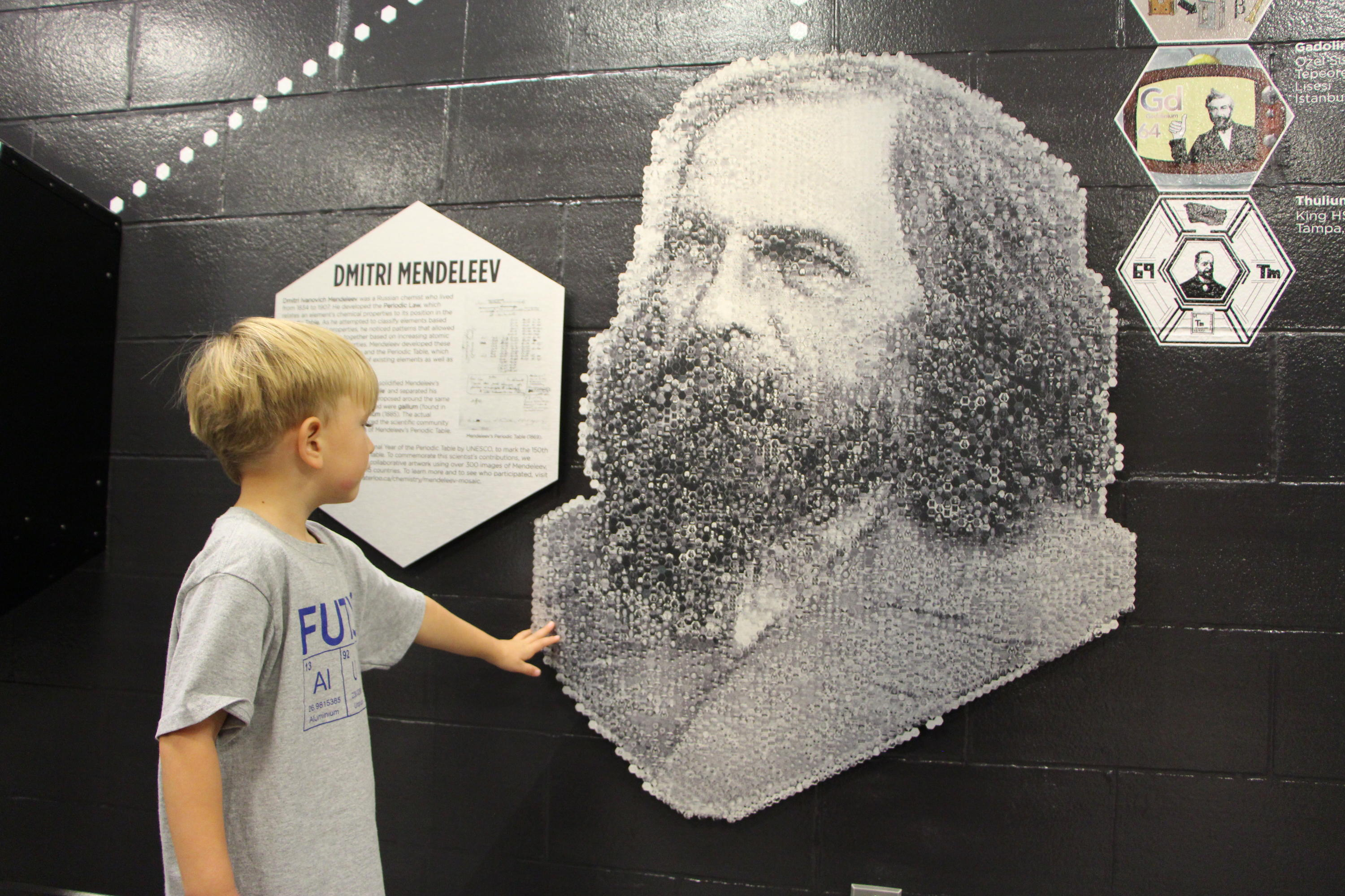 Child standing and looking at a mosaic of Dmitri Mendeleev.