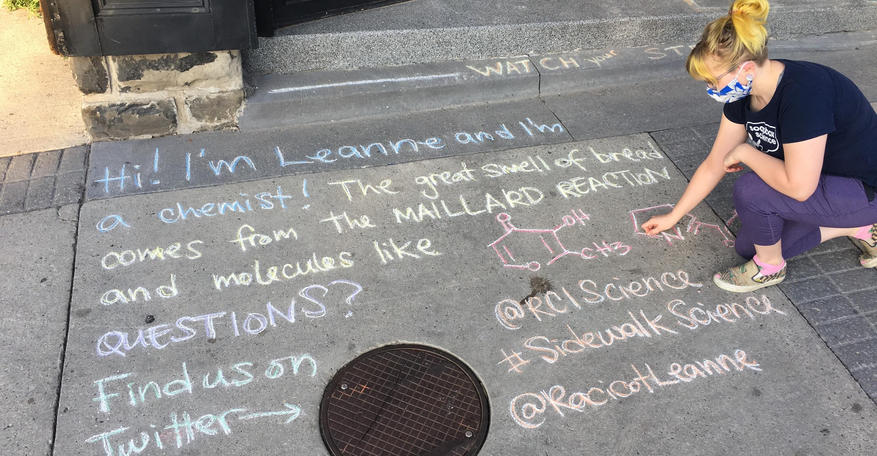 Woman writing about her research in chalk on the sidewalk