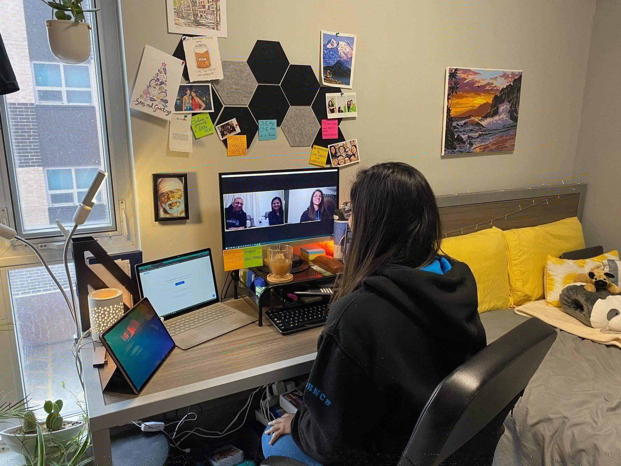 Divya sitting at a computer chatting with family on a video call
