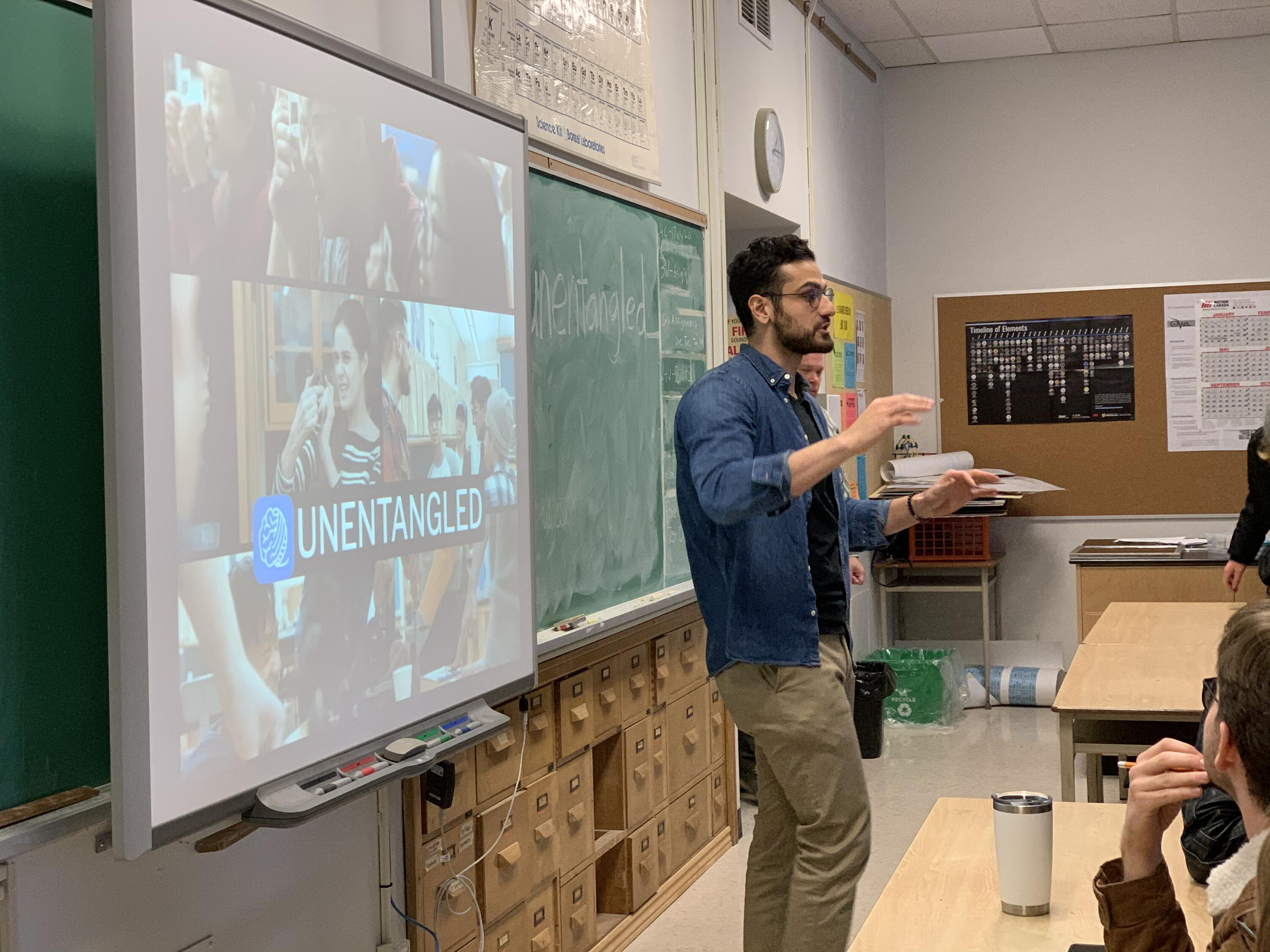 Shayan Majidy in front of a classroom of students teaching