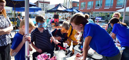 Let's Talk Science volunteer does a chemistry experiment with 3 children in front of Kitchener City Hall.