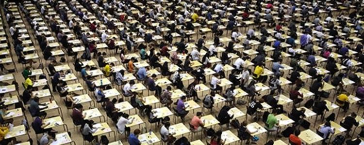 Mass number of students sitting at desks writing exams.