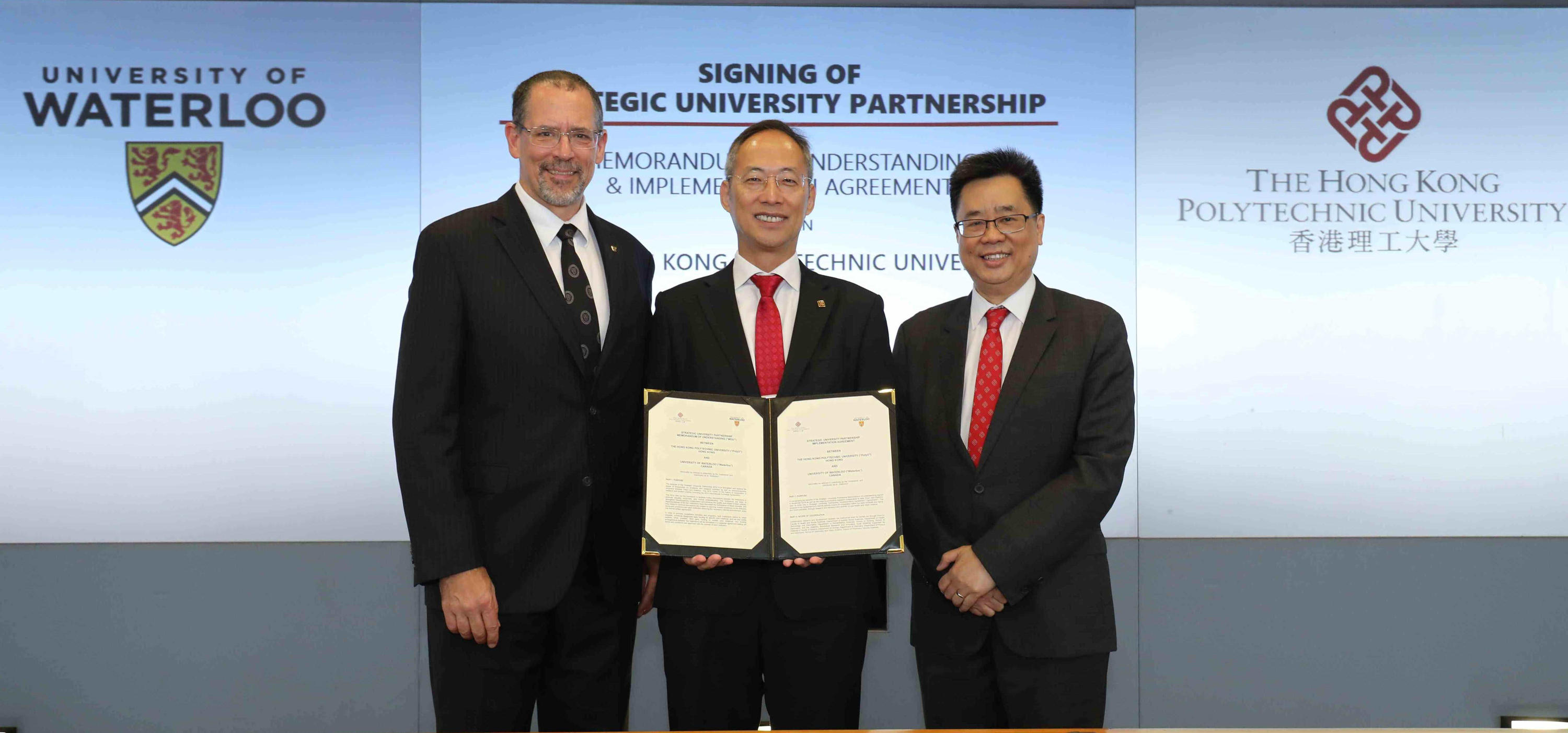 Alexander Wai holds signed agreement and poses with Bob Lemieux and David Shum.